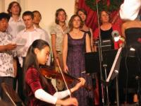 High school students singing with a middle-school student on strings